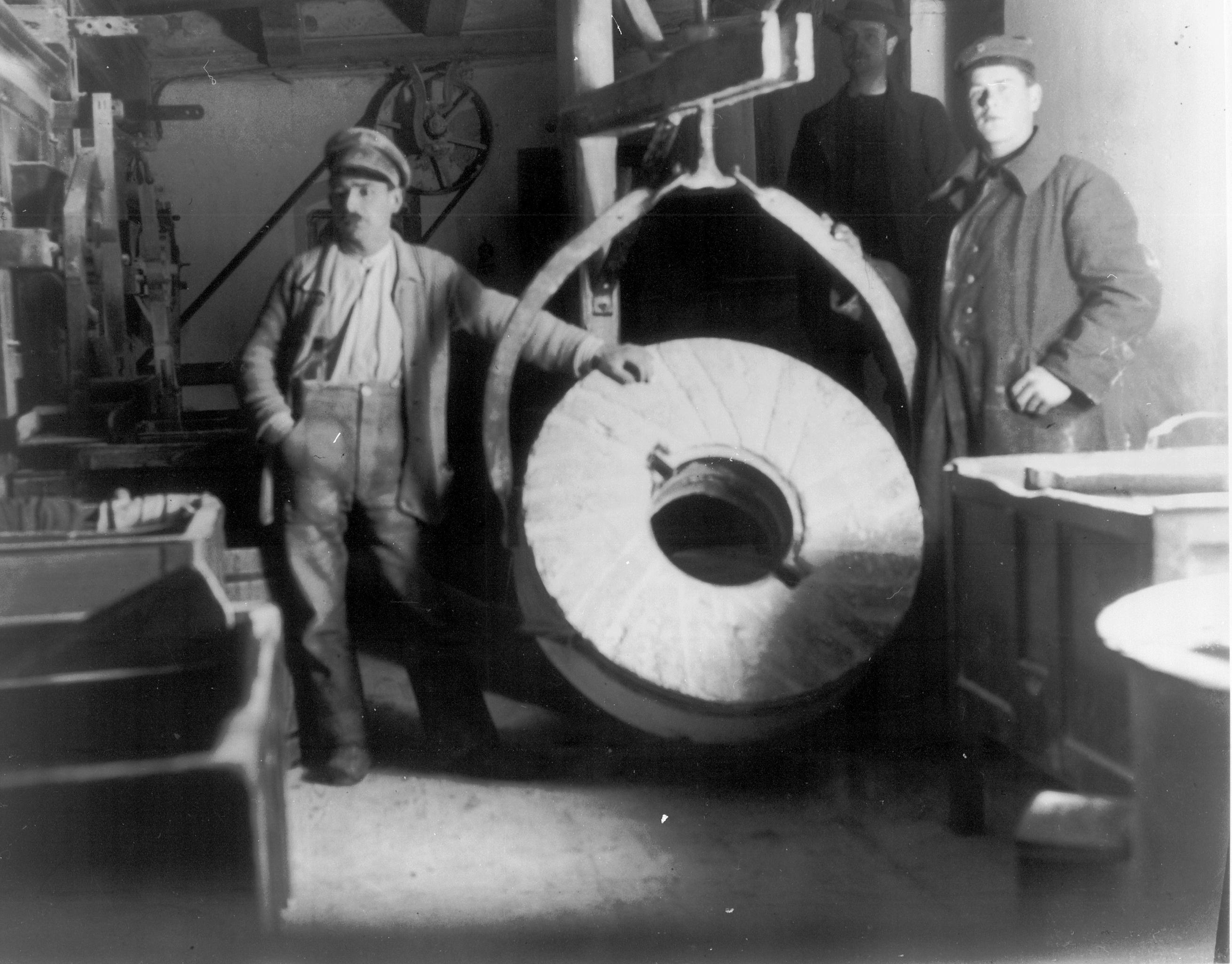 Links steht Urgrossvater Wilhelm Fessler vor dem Schrotgang, mit dem heute noch das Getreide vermahlen wird